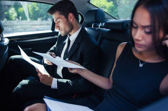 Deux personnes assises à l'arrière de la voiture travaillant sur papier et sur ordinateur portable. Cela montre que la voiture est agréable pour les passagers et que les personnes en retard ou voulant travailler plus vite peuvent le faire simplement.